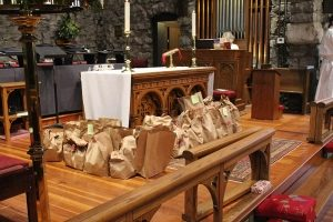 ABCCM Food Drive Bags Full of Food In Fron of Altar